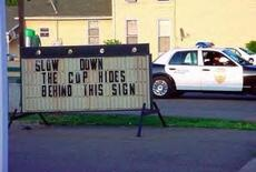 slow down the cops hide behind this sign